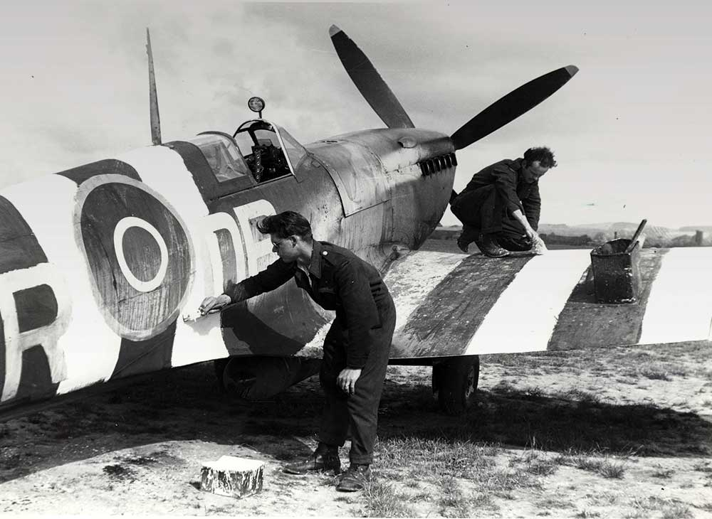 Aircraftman paint D-Day markings on an Allied aircraft.