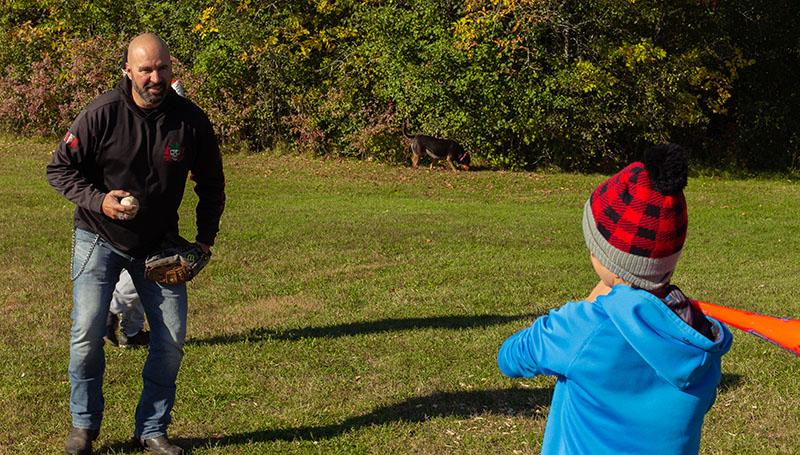 Bill lance une balle de baseball à son fils.