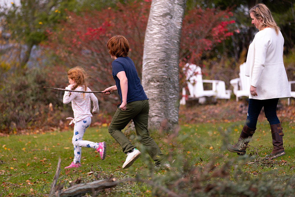 Kate walking with two of her children in the backyard.