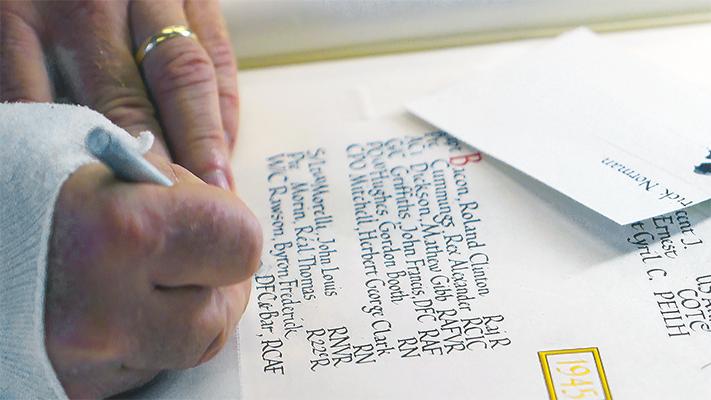 Un gros plan de la main de Richard Draffin inscrivant un nom dans les Livres du Souvenir.